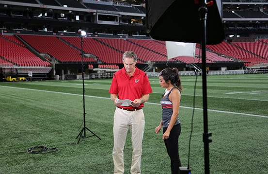 Financial advisor Chris Hoffman and TV host Annalee Penny prepare for a segment on location at Mercedez-Benz Stadium.